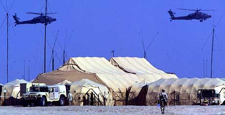USA har allerede store styrker i nærheten av Irak. På bildet flyr to apache-helikoptre over flere militære telt i leiren