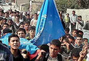 Palestinere bærer FN-flagg under en symbolsk begravelse av Iain John Hook. Foto: Reuters.
