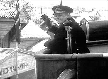 Kong Olav V helsar dei frammøtte på kaien på Hermansverk under jubiléet for Fylkesbaatane i 1958. (Foto: Norsk Film/NRK)