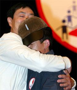 Skodespelaren Pu Cunxin omfamnar ein aids-sjuk for å vise at slik kontakt ikkje er farleg. (Foto: Guang Niu, Reuters)