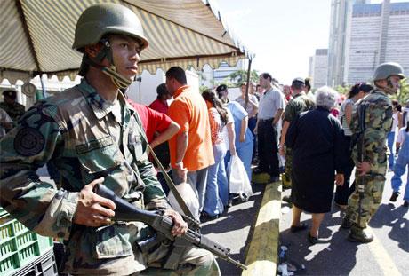 En soldat passer på under en streikemarkering i Caracas i dag. (Foto: Kimberly White/Reuters)