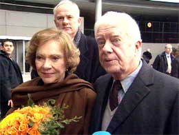 Jimmy Carter med seg sin kone Rosalynn under mottakelsen på Gardermoen i formiddag. I bakgrunnen direktør ved Nobelinstituttet, Geir Lundestad. Foto: NRK