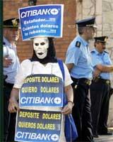 Maskert demonstrant krever pengene sine tilbake ( REUTERS/Enrique Marcarian)