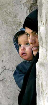 En irakisk kvinne og hennes barn er vitne til at våpeninspektørene kommer til stedet. Nå øker krigsfrykten i landet. (Foto: Reuters/Scanpix)