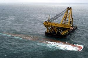 """Et bilde av """"Tricolor""""-vraket tatt 23. desember. En kran tømmer vraket for olje. (Foto: Reuters)"""