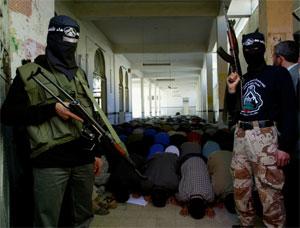 Væpnede aktivister fra Al Aqsa-brigradene holder vakt ved en moske i Khan Yunis på Gazastripen søndag. (Reuters-Scanpix-foto)