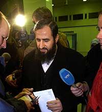 Mulla Krekar får tilbake papirene av representantene fra de nederlanske immigrasjonsmyndighetene som fulgte ham til Gardermoen. Foto: Tor Richardsen, Scanpix
