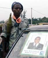 En opprørssoldat vest i landet med bildet av general Guei, som ble drept ved byen Man (REUTERS/Luc Gnago)
