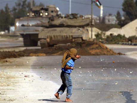 En palestinsk 11-åring kaster stein mot israelske soldater under en israelsk militæraksjon på Gazastripen. (Foto: Reuters/Scanpix)