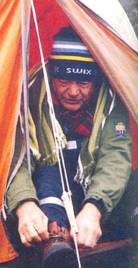 Tidlig morgen sittende i teltåpningen i P1-leiren i Tiklanika i Alaska knytter Rolf Kirkvaag skoene.