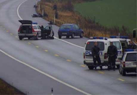 Politiet gjemte seg bak skjold da de tok seg fram til bilen der den sårede mannen lå ( Foto: Jon Fredheim )