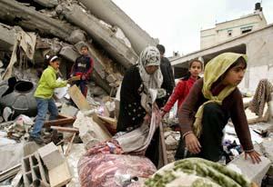 En palestinisk mor og hennes barn leter etter eiendeler i ruinene huset deres, som ble ødelagt i dag tidlig. (Foto: M.Ribeiro, Reuters)