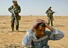 I SIVIL: De amerikanske marineinfanteristene ser seg vaktsomt omkring mens en irakisk mann de tror kan være soldat, kneler på bakken (Foto: Oleg Popov/Reuters).