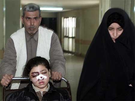 En skadd irakisk pike følges av sine foreldre på skehus i Bagdad etter torsdagens bombing. Foreldrene sa hun ble skadd i det amerikanske angrepet. (Foto: Reuters/Akram Saleh)