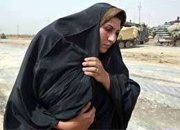Irakisk flyktning fra Bagdad prøver å beskytte barnet sitt mot heten på landeveien (REUTERS/Oleg Popov)