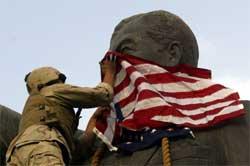En amerikansk marinesoldat danderer et amerikansk flagg rundt hodet til Saddam-statuen. Foto: Reuters/Goran Tomasevic.