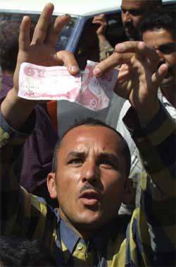 En iraker river i stykker en dinar-seddel med Saddams portrett i Mosul. (Foto: Reuters/Caren Firouz)