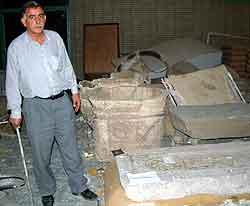 En av de ansatte ved nasjonalmuseet i Bagdad viser frem ødelagte antikviteter fra Mesopotamia. Foto: Kyodo, Reuters