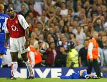 UTE: Sol Campbell ser en annen vei mens Ole Gunnar Solskjær ligger nede etter å ha fått Arsenal-spillerens albue i hodet (Foto: Ben Radford/Getty).