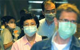 Flypassasjerer i Singapore bærer masker i et forsøk på å forhindre spredning av det dødelige viruset (foto: Getty Images)