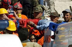 Tyrkiske redningsarbeidere bærer ut skolegutten Enes Kunce, som lå under ruinene i 30 timer. (Foto: F.Saribas, Reuters)