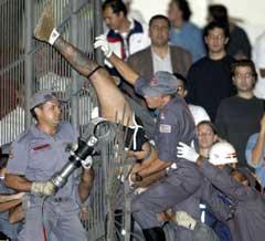 Brasiliansk politi hjelper en Corinthians-fans som hadde satt seg fast i gjerdet under kampen mot River Plate. (Foto: Paulo Whitaker/Reuters)