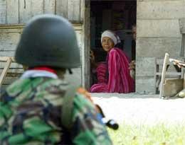 Kvinne i Aceh betrakter en indonesisk soldat etter et sammenstøt mellom hæren og separatiskbevegelsen GAM i dag (Reuters)