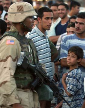 En amerikansk soldat patuljerer blant folkemengden i Bagdad. (Foto: Reuters/Scanpix)