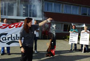 PROTESTERTE: Tou-ansatte protesterte mot Ringnes-ledelsen på bryggeriet i Stavanger onsdag morgen. Flere ansatte markerte sin avsky mot nedleggelsesplanene ved å brenne T-skjorter og annet Tou-utstyr. (Foto: Alf Ove Hansen / SCANPIX)