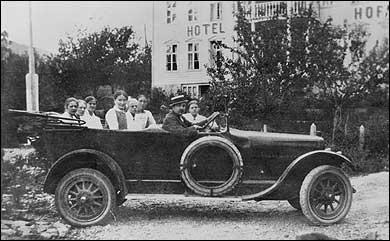Sjåfør Anton Andersen med og passasjerar i den første rutebilen i Sogndal, utanfor Hofslund hotell. (Foto © Fylkesarkivet)