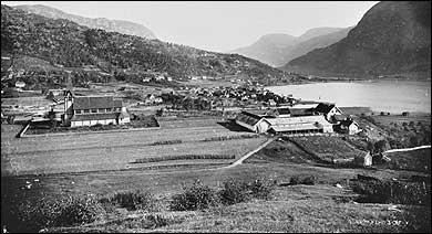 Øvre del av Stedje i 1880. Til venstre ligg Stedje kyrkje. I bakgrunnen er Sogndalsfjøra. (Foto © Fylkesarkivet)