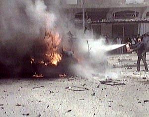 En palestiner prøver å slokke en bilbrann etter det første angrepet i dag. (Foto: Reuters).