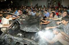 Palestinere forsøker å slukke en bil som brenner etter et israelsk rakettangrep i Gaza by fredag kveld. (Foto: Suhaib Salem/Reuters)