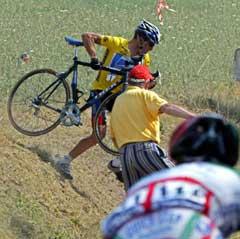 PÅ JORDET: Lance Armstrong løfter sykkelen over grøfta og inn på veien etter å ha krysset et jorde for å ikke kjøre på den veltede Beloki (Foto: AFP/Scanpix).