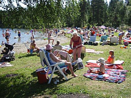 Badegjester koser seg på Landfalltjern i sommervarmen, men mange kaster fra seg søppel og griser til badestedet.