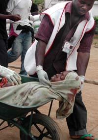 En kvinne såret av en rakett som havnet blant flyktningene i Monrovia kjøres i trillebår til sykehuset. (Foto: P.Flomoku, AP)