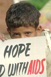 Sønnen til en prostituert i Bombays røde kvarter holder opp et banner som utrykker håp om en bedre framtid (Scanpix/AP)