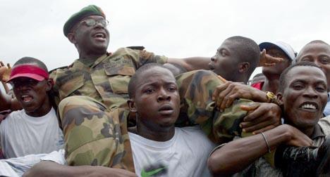 JUBEL: En liberiansk soldat blir båret på skuldrene ved ankomsten til Monrovia i dag (Foto: AP/ Scanpix).