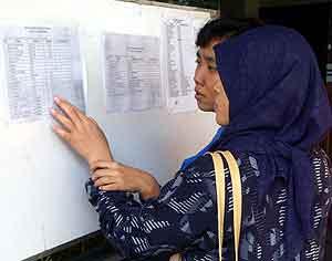 To kviner leser listene over ofrene for bomben i Mariott-hotelet i Jakarta onsdag. Foto: Suzanne Plunkett, AP
