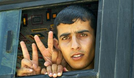 V-TEGNET: Palestinerne viste v-tegnet ut av bussvinduene da de ankom leiren i nærheten av Ramallah (Foto: AP/ Scanpix)