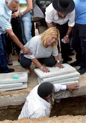 Systera til ein av dei drepne i sjølvmordsaksjonane i går fotografert under graverda. (Reuters-foto)