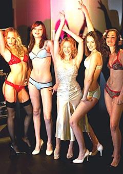 Kylie Minogue (påkledd) i midten av modeller som viser kreasjoner fra hennes nye undertøyskolleksjon LoveKylie. Foto: Kieran Doherty/Reuters / SCANPIX.