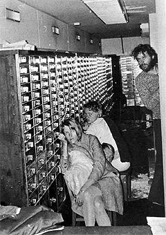 Bankraneren Clark Olofsson til høyre, skuler mot kamera mens to kvinnelige gisler sitter i bankvelvet 23. august 1973. Fotografiet ble tatt med et kamera som ble senket ned i et hull i taket. (Foto: Svensk Politi/AP)