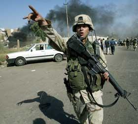 Ein amerikansk soldat omdirigerer trafikken etter en eksplosjon. (Foto: Suhaib Salem / Reuters / Scanpix)