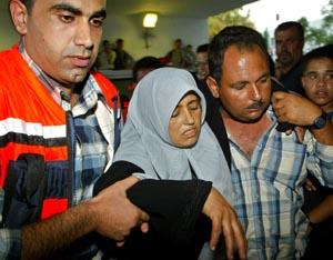 En såret kvinne får hjelp av medisinsk personell etter å ha blitt såret i helikopterangrepet i Israel i dag (Foto: Scanpix).