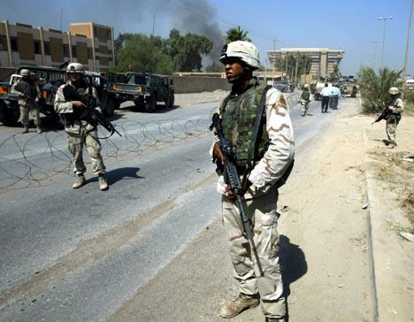 En amerikansk soldat bevokter den eksplosjonsrammede politistasjonen i Bagdad. Foto: Peter Andrews, Reuters/Scanpix.