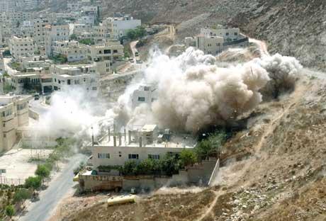 Røyken stiger opp fra ruinene av høyblokken som ble sprengt under jakten på en Hamas-leder (Scanpix/Reuters)