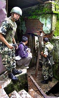 Nepalske soldater undersøker en kontorbygning etter en av bombe-eksplosjonene i Katmandu (Foto: Scanpix).