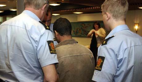 Den tiltalte i drapsaken blir følgt ut av to politibetjenter under en pause i rettsaken som gikk i Valdres tingrett. (foto: Scanpix)