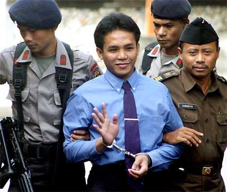 Imron Ali vinker til de frammøtte mens han blir ført inn i rettssalen av to politimenn. (AFP-foto)